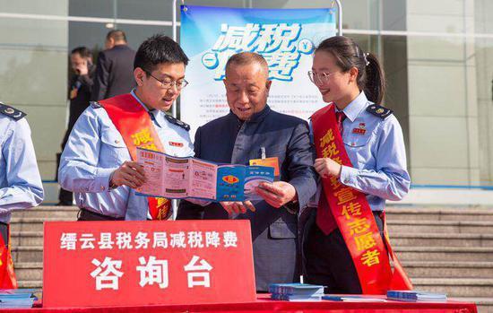 税务人员向纳税人介绍电子税务局操作应用手册。 浙江省税务局供图