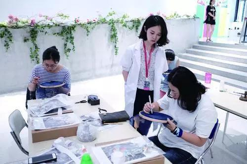 张晓星(中)在给学生上刺绣课