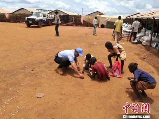 警队副队长何斌帮助难民儿童捡拾散落的米粒 浙江公安 供图