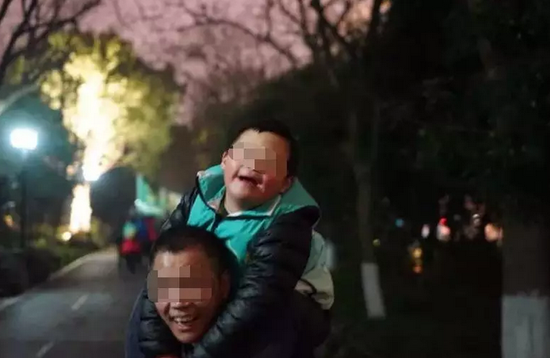"""""""拼命三郎""""背着儿子微笑面对未来。记忆 摄"""