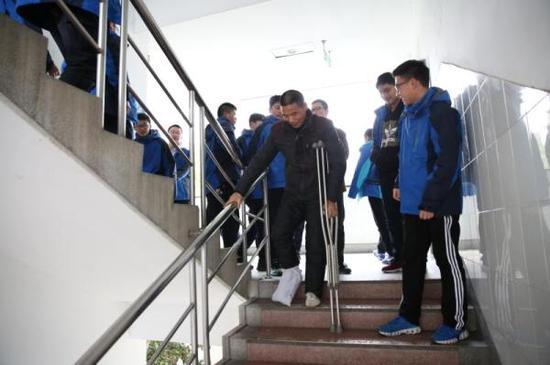 周炎宏下楼拒绝学生搀扶。