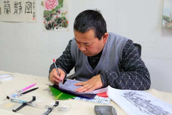 图为:唐师傅正在办公室里专心创作叶雕。 王远 摄