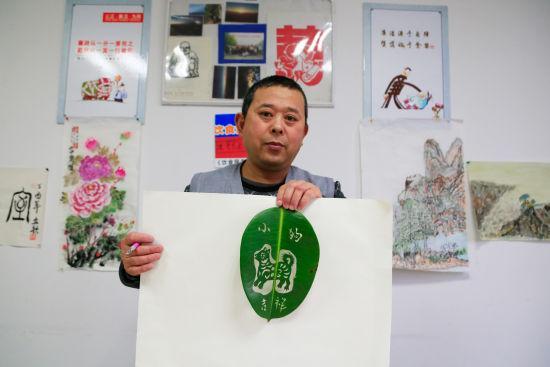 """图为:唐师傅正在展示刚刚完成的雕刻作品""""小狗吉祥""""。 王远 摄"""