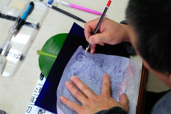 图为:唐师傅正在用复写纸将事先画好的图案描到树叶上。 王远 摄