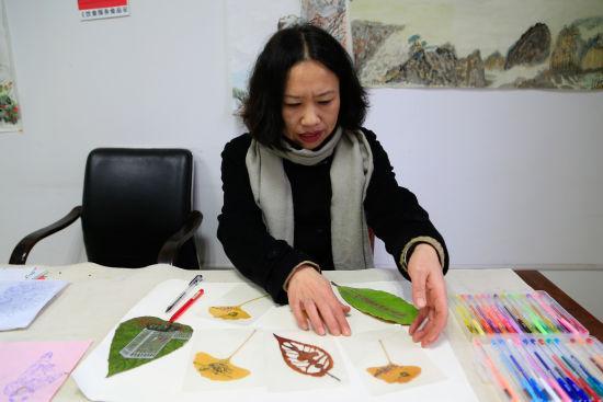 图为:齐阿姨正在展示自己在树叶上所作的绘画。 王远 摄