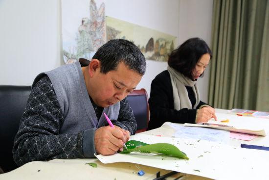 图为:唐师傅与齐阿姨正在专注于各自的创作。 王远 摄