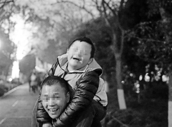 """上图:""""拼命三郎""""背着儿子微笑面对未来。 记忆 摄"""