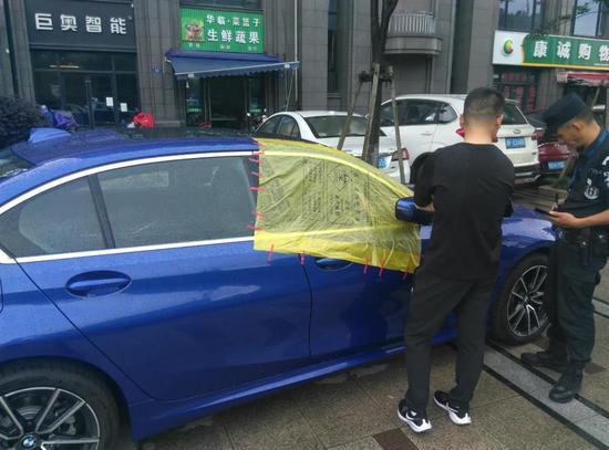 杭州一男子下雨天在车旁守护两小时 车内有几千块现金