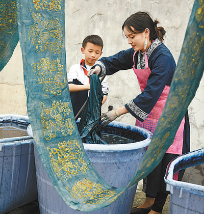 冉光津(右)在给工艺服饰染色。记者 杨文斌 摄