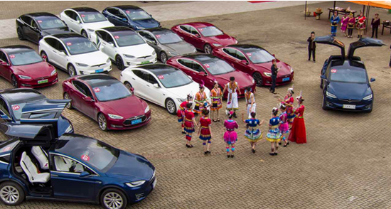 在东西岩景区,畲族姑娘与特斯拉车队热情互动