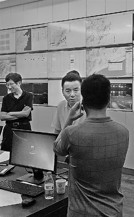 朱家驹(背对镜头打电话的)和同事们正在紧张工作中