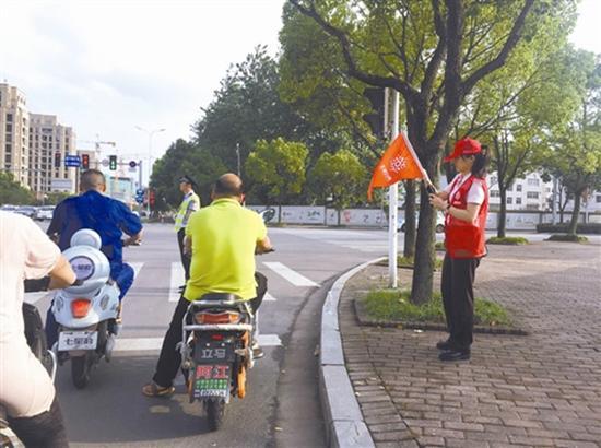 """在马路上进行文明劝导的""""红马甲"""",图片来源:台州商报"""