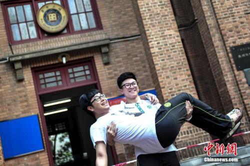资料图:一名高考考生抱起同学在考场前合影留念。 陈骥旻 摄