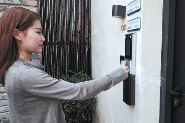 工作人员演示通过验证身份证和人脸识别打开房门。 摄影/新京报记者 王嘉宁