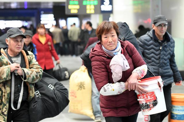 杭州外来务工者肩扛手拎行李 踏上返乡之路