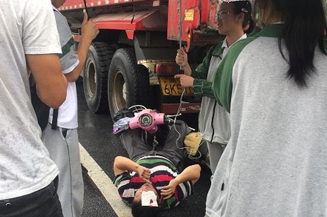 杭骑车男子撞上卡车血流不止 学生为其撑伞拨打120