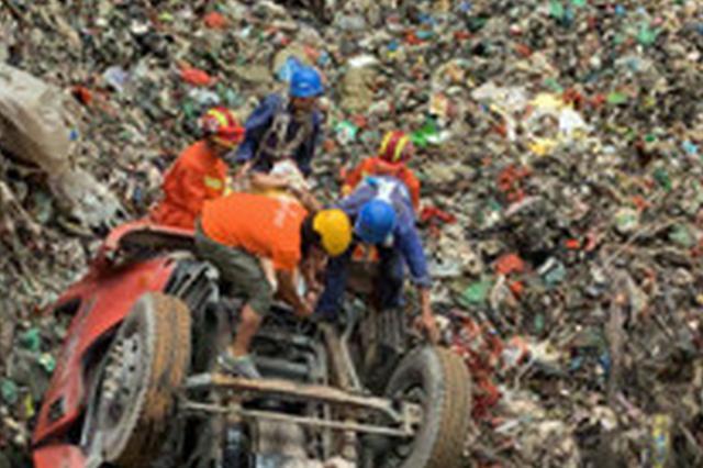 浙江1垃圾车翻入10米堆放槽 消防员顶着恶臭救援