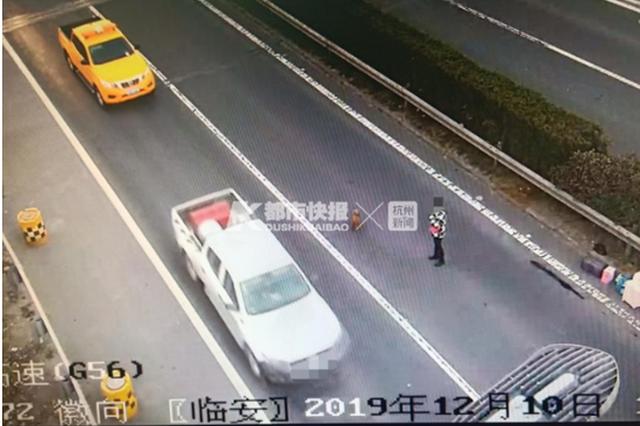 杭州一男子超车道上换轮胎 女子后方摇旗做预警