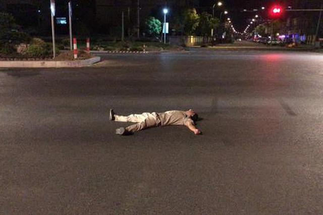 车来车往的公路上 嘉兴一男子躺在十字路口呼呼大睡