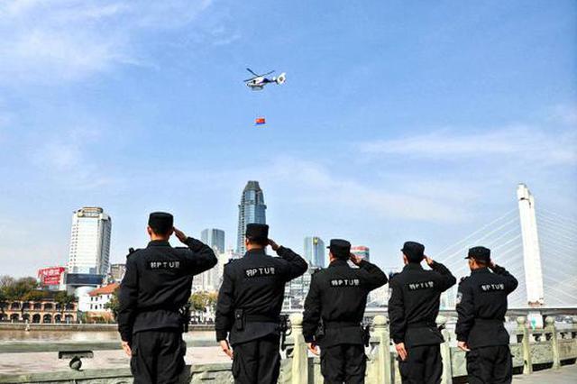 警航队直升机悬挂警旗飞过三江口 现场人员向警旗敬礼