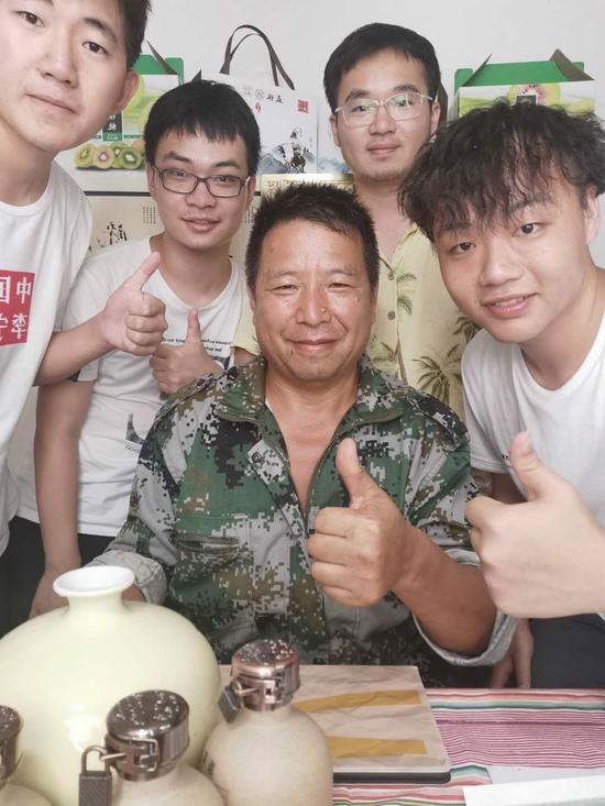学生团队和美女峰家庭农场的胡宏伟一起直播销售猕猴桃酒