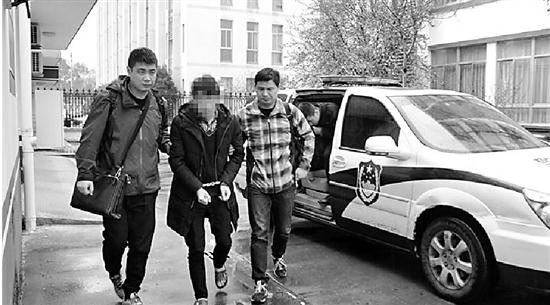 嫌疑人龙某(中)被警方从湖南带回。