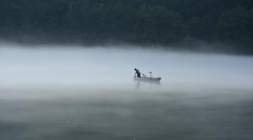 杭州渔民划小船 在缥缈奇雾中拉起渔网