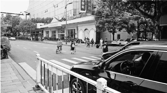 体育场路永天路口,早高峰过马路的行人络绎不绝,礼让的车辆排起长龙。