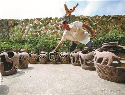 宁海桥头胡街道一村民在酒甏上雕刻图案 将酒甏做成盆景