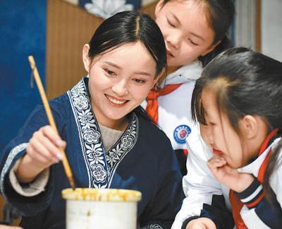 """冉光津(左一)在给学生示范""""枫香染""""绘制技巧。记者 杨文斌 摄"""