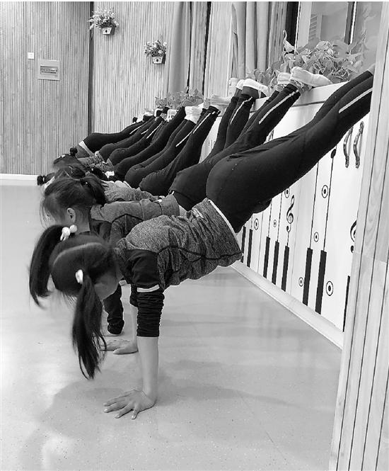 杭州滨江区东冠小学学生,放学后在老师指导下练习健美操。