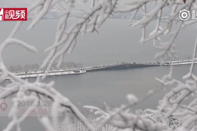 杭州西湖雪后银装素裹如画 游人漫步雪上
