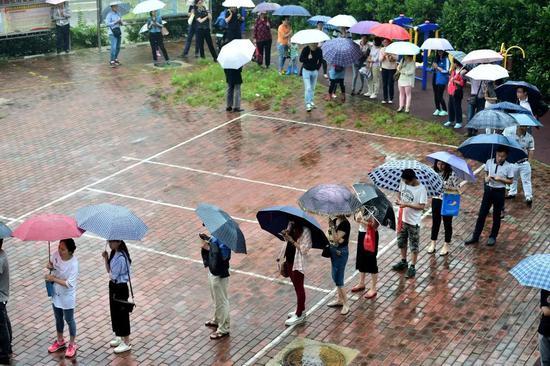 (2016年6月8日,经合肥森林海幼儿园前期资格审查合格的家长们在排队等候抽签摇号。新华社记者刘军喜摄)