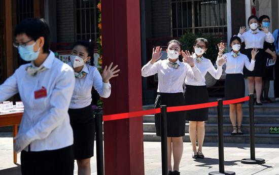 """5月26日,北京光明小学进行返校复课准备工作全流程演练。在校门口,教师排队欢迎""""学生""""。"""