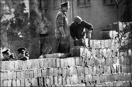 东德士兵和工人正在给柏林墙增加高度