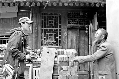 在老房门前,杨广全老人向贾元良讲述傅作义将军抗战时期的故事