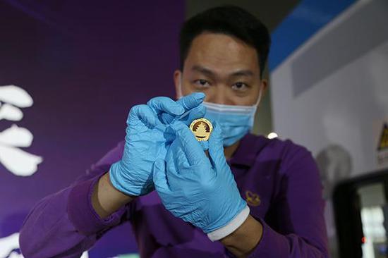 鑄幣機機長開啟印花機成功鑄造第一枚2021版熊貓金幣