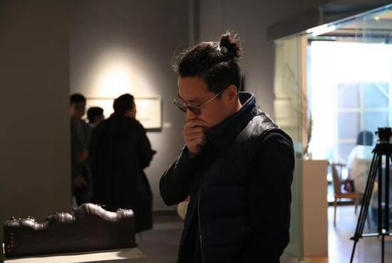 展览现场,独立策展人王澈观看作品