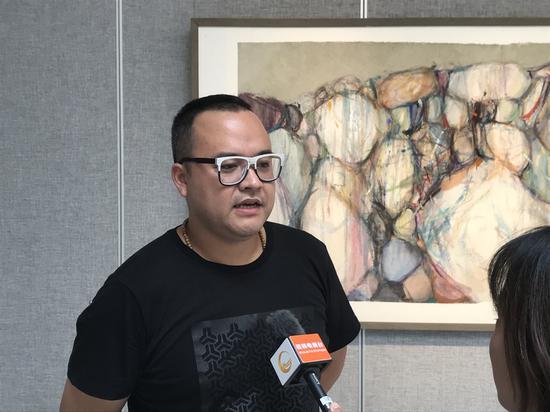 本次展覽策展人、桂林市花橋美術館館長助理黃嘯偉接受本地電視臺采訪