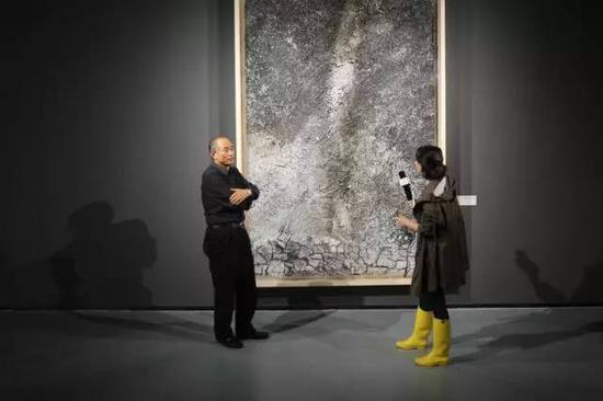 严陆根博士给正在百家湖美术馆参观基弗展的记者讲解作品