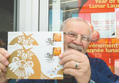图为一名集邮者展示他购买的狗年邮票首日封 人民视觉