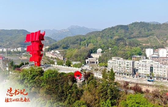 """△2021年4月9日拍摄的鄂豫皖苏区首府革命博物馆附近英雄山上的""""红旗飘飘""""主题雕塑。雕塑高28米,象征着鄂豫皖苏区28年红旗不倒(无人机照片)。"""