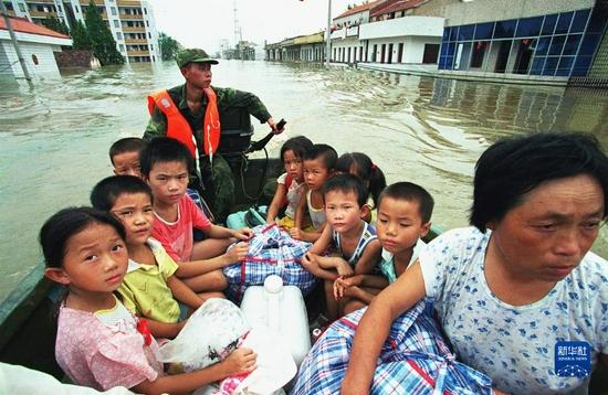 在湖北省嘉鱼县一片汪洋的水面上,一支解放军舟桥部队用冲锋舟载着灾民在茫茫洪水中寻找返回的路线(1998年8月摄)。新华社发(资料照片)