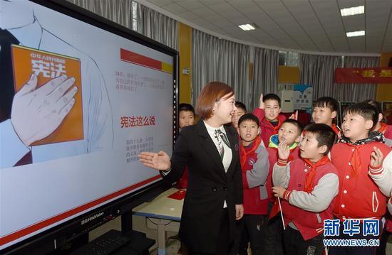 安徽省合肥市经开区明珠居委会法律援助律师在给明珠小学的学生们讲解宪法知识(2018年12月3日摄)。 新华社记者 郭晨 摄