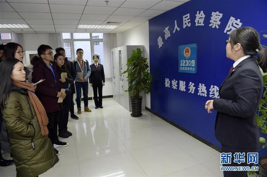 2018年12月4日是国家宪法日,最高人民检察院机关举行第26次检察开放日活动,这是参加开放日活动的代表在参观12309检察服务中心。 新华社发