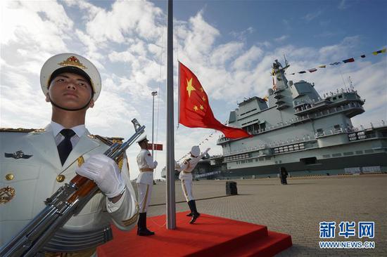 """2019年12月17日,我国第一艘国产航空母舰山东舰在海南三亚某军港交付海军。经中央军委批准,我国第一艘国产航母命名为""""中国人民解放军海军山东舰"""",舷号为""""17""""。这是交接入列仪式现场。 新华社记者 李刚 摄"""