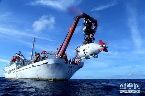"""在西太平洋海域,""""蛟龙""""号载人潜水器离开""""向阳红09""""科学考察船准备进入水中,进行中国大洋38航次最后一潜(2017年6月13日摄)。 新华社记者 刘诗平 摄"""