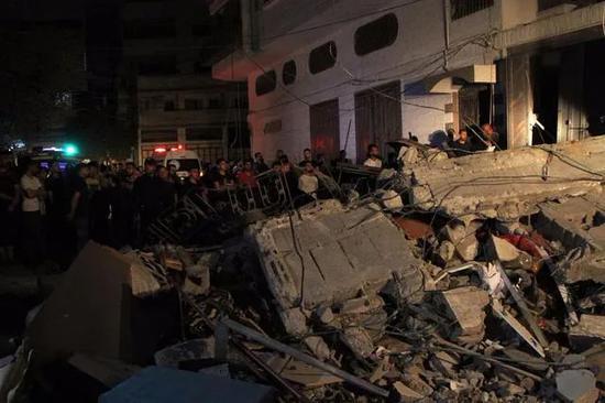 5月15日,人们聚集在加沙城一处遭空袭的难民营 图:新华社