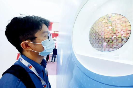 参观者在2020中国国际半导体博览会上观看中芯国际生产的芯片。图/IC