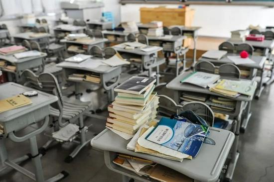 2017年2月24日,北京一家重点中学在房山开设的分校区里,一个上体育课而空出来的教室,课桌上堆满了书本。/视觉中国
